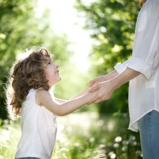 parent holding girl's hands - authoritative parenting is the best among the 4 styles of parenting
