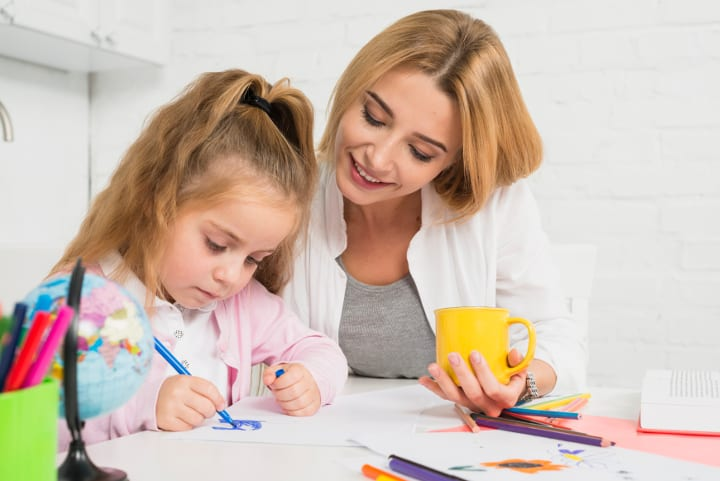 Woman happily watches girl do homework. She gets 4 year old to do homework.