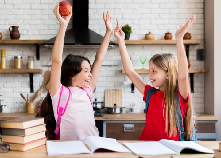 Two girls with backpacks raise their hands and laugh, one holding an apple - Resilient