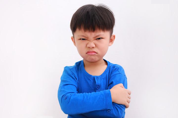 an angry disrespectful boy in blue shirt
