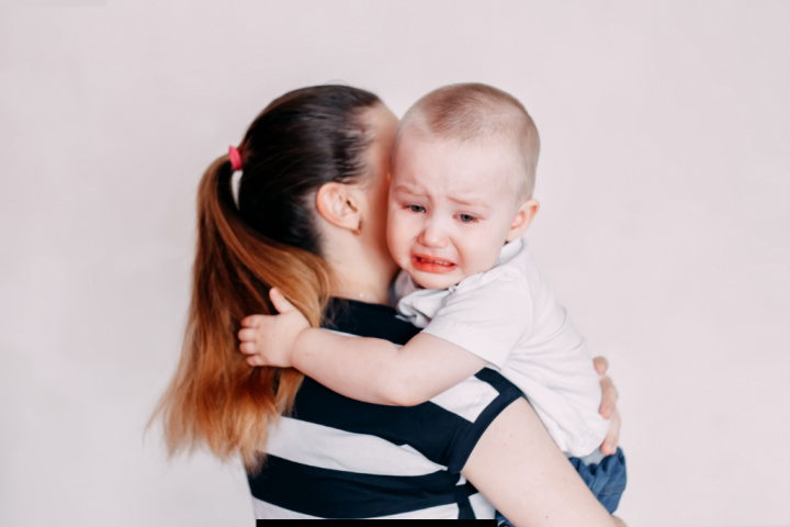 boy anxiously attached to mother crying