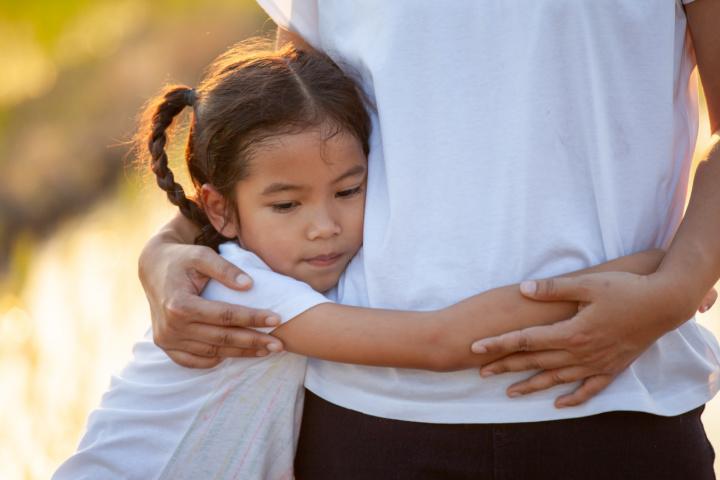 anxious girl hugs parent