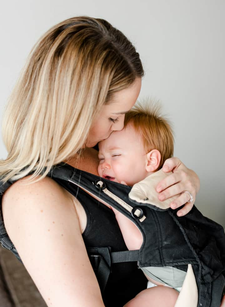 Woman carries a sleepy baby in a carrier - what is attachment parenting and its effect on brain development
