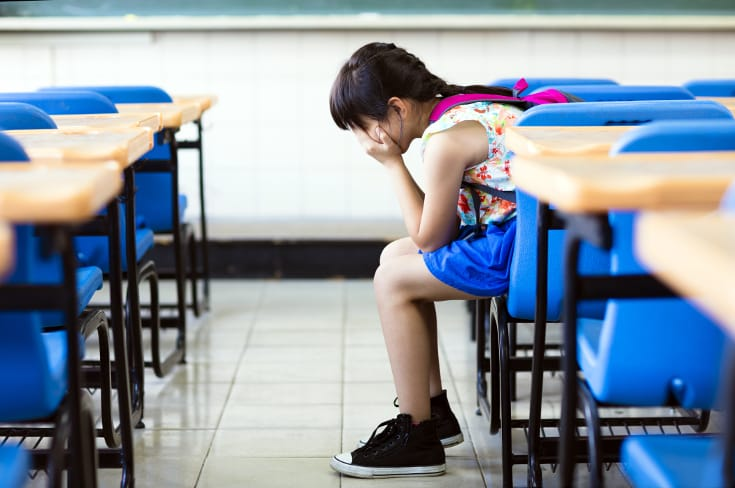 Girl buries her face in palms and sits alone in classroom - detrimental effect of authoritarian parenting style