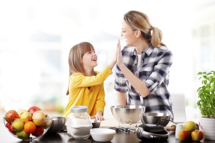 Mother daughter high-five - authoritative parenting is unlike conventional parenting.