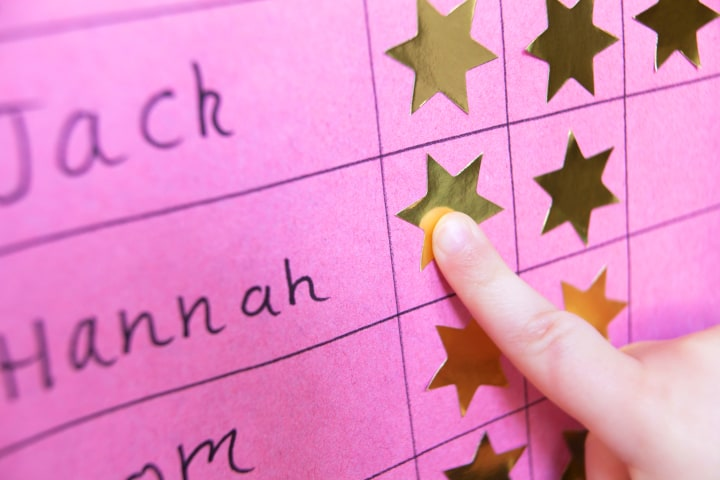 A child points at a gold star on the behavior chart.