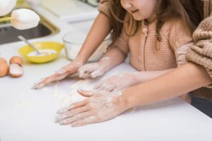 parent and child make dough on table - benefits of sensory play