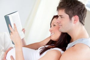 Close-up of a pregnant woman and her husband reading a book on bed - best parenting books