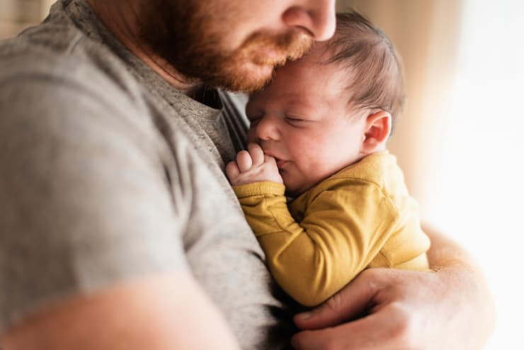 Father hugs sleeping infant, fitting the bowlby attachment theory