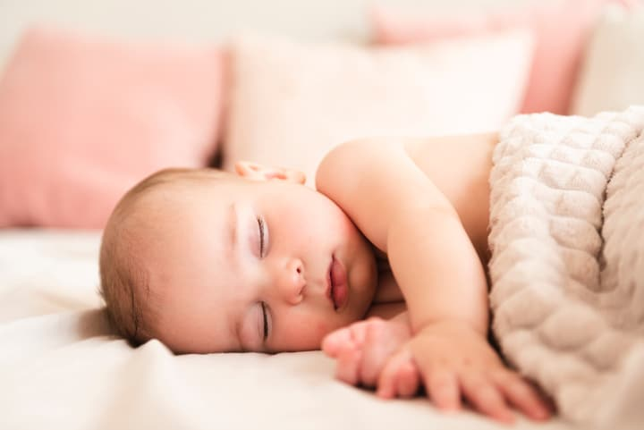 Baby sleeps peacefully on bed - bowlby attachment theory