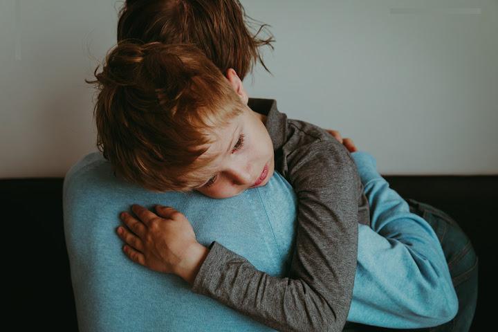 boy crys on mother shoulder