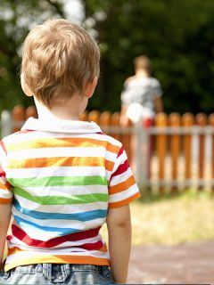 boy looks at the back of parent behind fence
