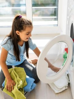 girl washes the dishes at the kitchen sink, one of the chore chart items