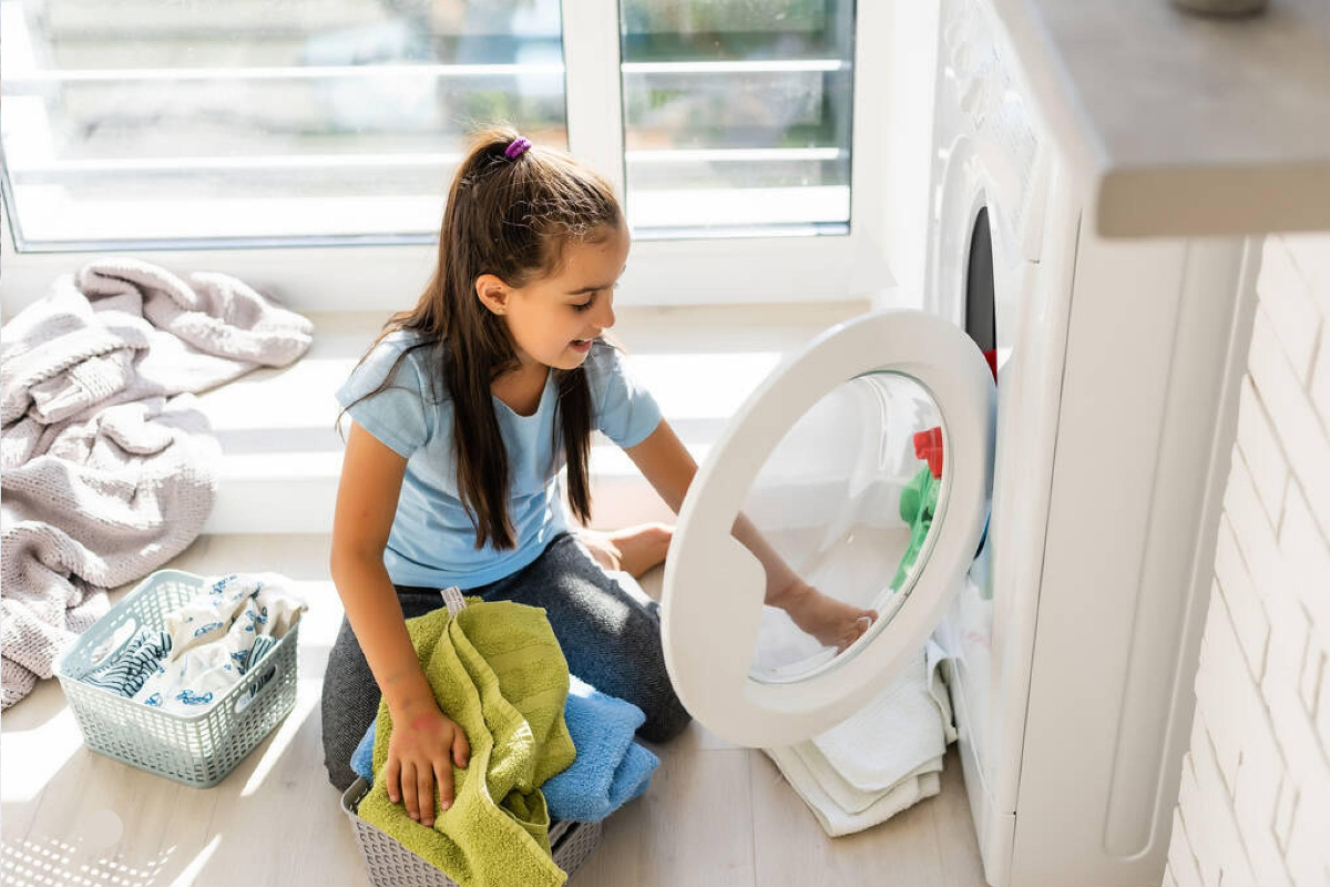 a girl in a red checker outfit washes the dishes at the kitchen sink, showing how to get a child to do chores.