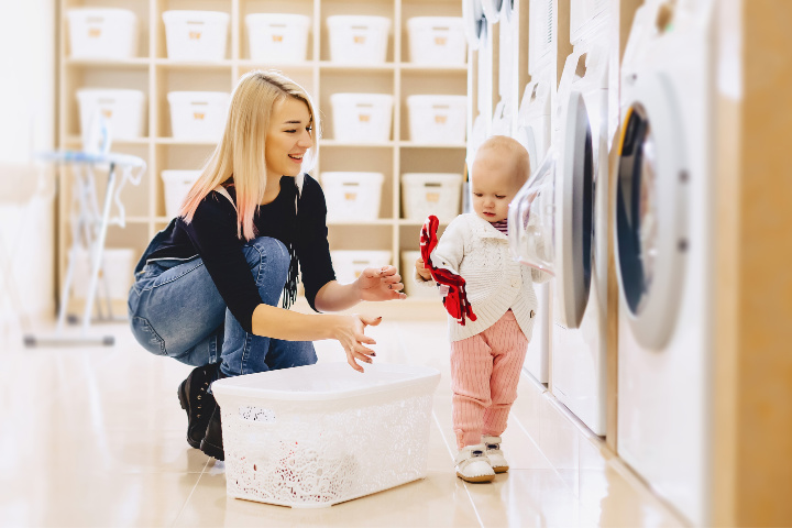 A toddler helps mom put laundry into the washing machine in the laundry room. Doing chores for kids is a good way to instill family values when it's done right.