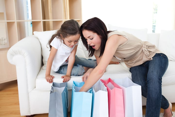 Child and woman are excited to check out what is in the 5 colorful shopping bags. Classical conditioning causes them to feel excited even before seeing what's exactly inside.
