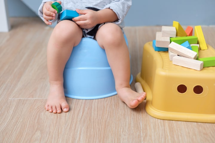 toddler sits on a potty while playing with toy blocks (example of difference between conditioning)