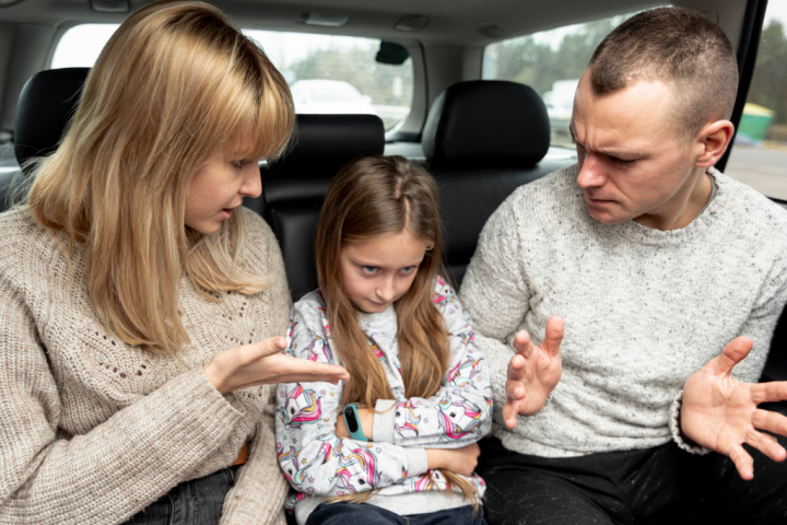 Controlling mother and dad are berating girl in the backseat of the car - controlling parents pscyhology