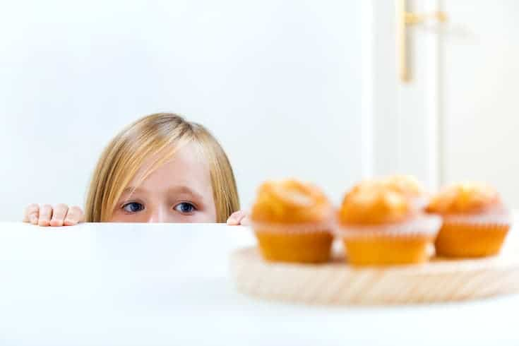 Girl peeks at cupcakes - the difference between positive and negative reinforcement