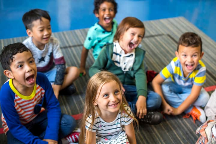Happy preschoolers listening - early childhood education