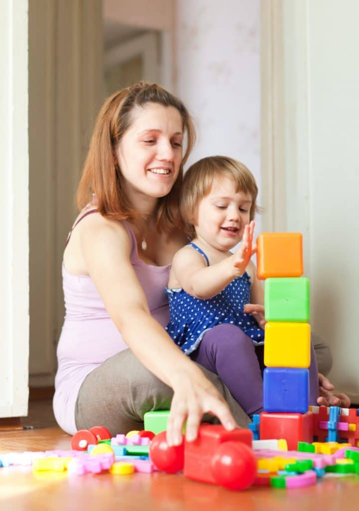 Parent encourages girl to stack up blocks high - how to praise kids with words