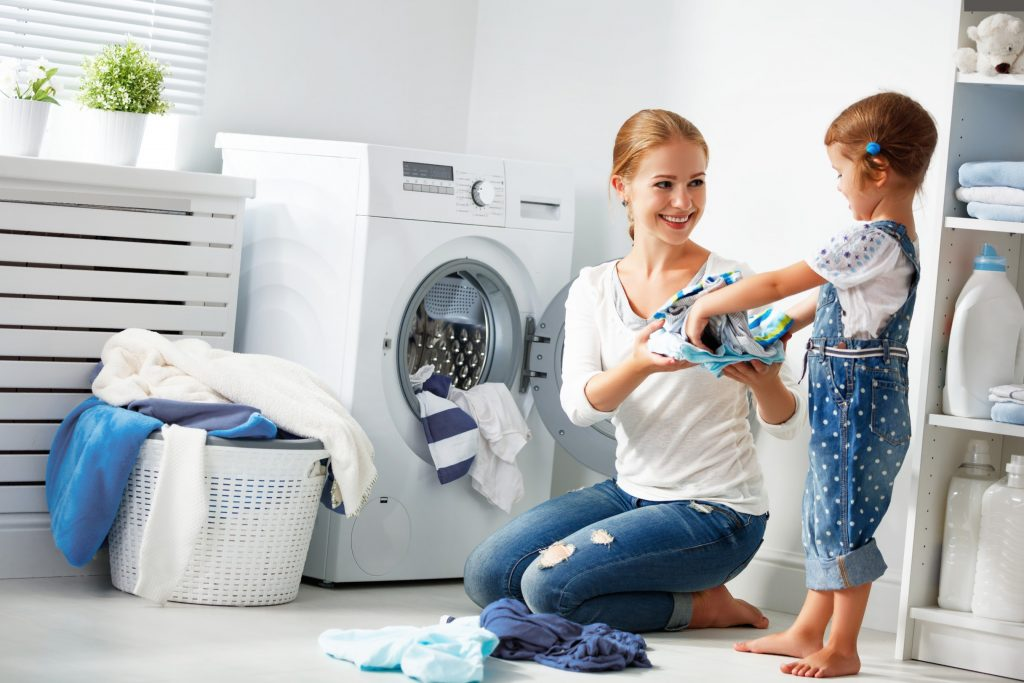 Girl helps mom do laundry. Both are smiling, great examples of having manners at dinner table