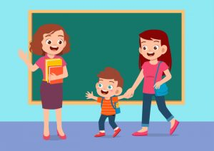 mom and boy greet teacher in the classroom in front of the blackboard