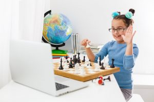 girl raises hand playing chess in front of a laptop