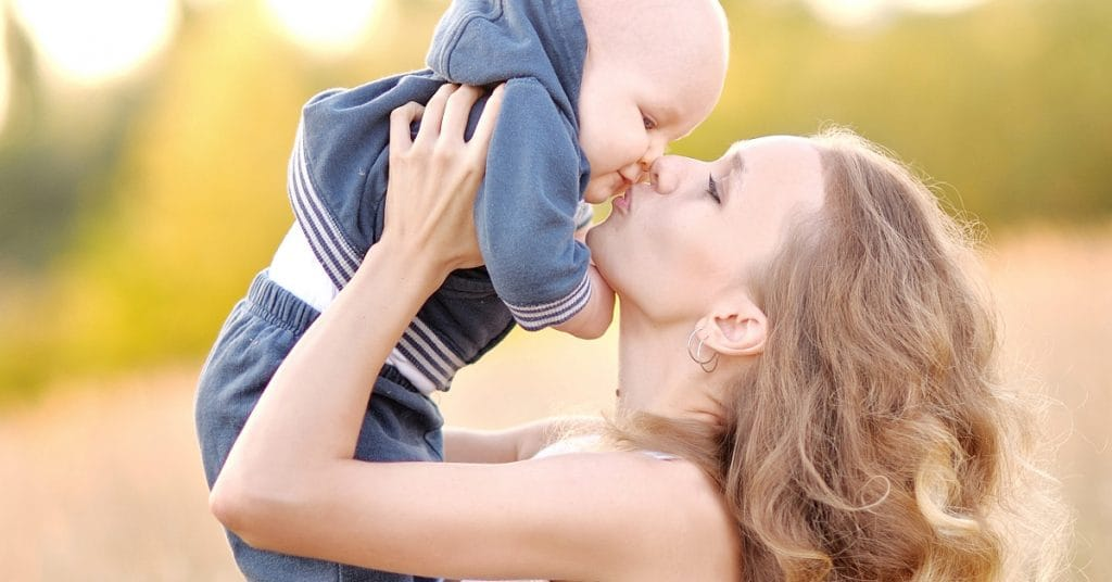 mother lovingly kisses baby - Good parenting tips