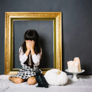 Girl covers up face in front of a golden picture frame - how to toughen up your kid