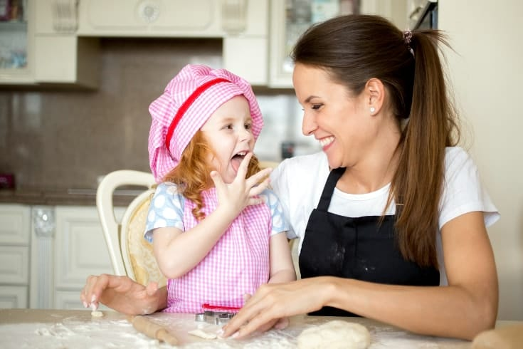 Mom praises girl dressed in pink apron as she licks her finger after making a dough - Words of Encouragement For Kids