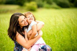 Mother hugs girl in a green field - hug benefits