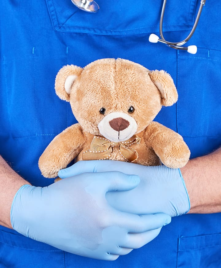 Man in scrub holds teddy bear - hugging