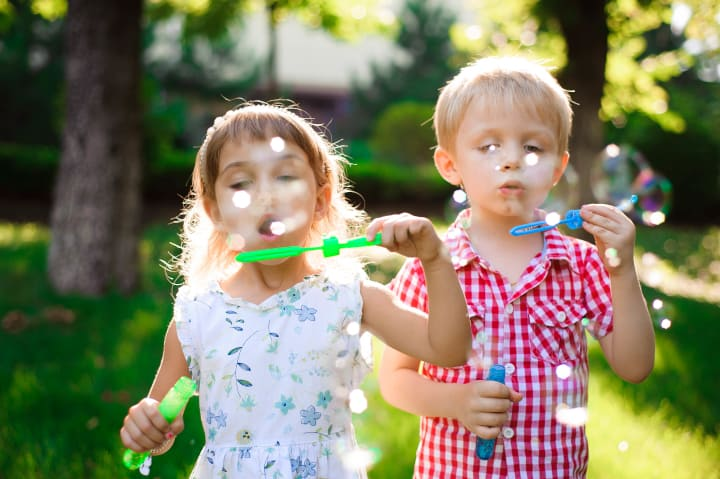 a boy and a girl blow bubbles in the park - importance of play