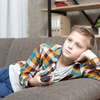 Boy lies on couch watching tv - What motivates your child