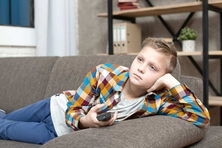 boy lays on couch watching tv, find out What motivates your child