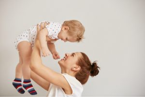 Mother holds baby up high and smiles at him forming a secure internal working model
