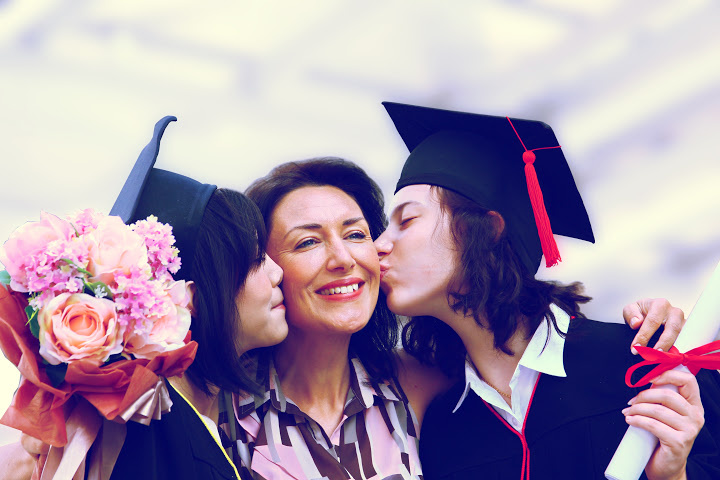 two daughters kiss mom when they graduate