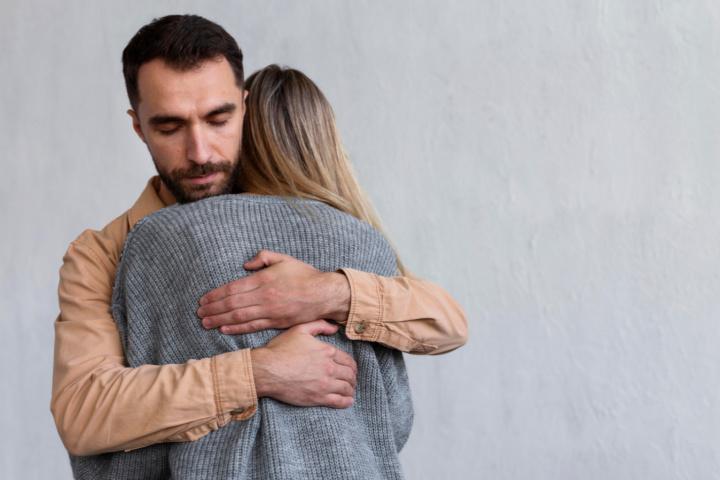 man hugs anxious woman
