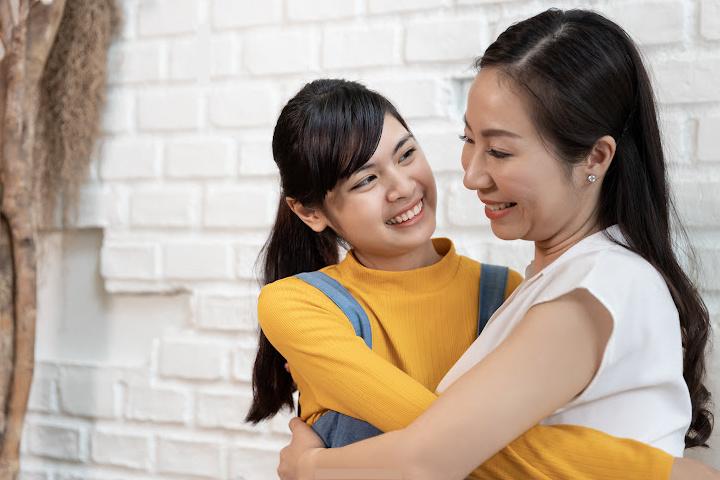 mom hugs daughter smiling