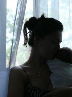 mom kisses baby in the dark