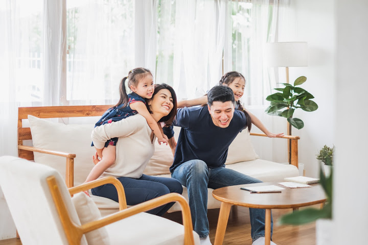Mom dad kids play together in the living room have close relationships parenting styles