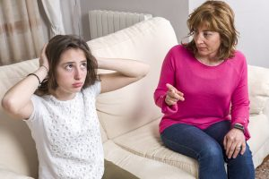 mother talks girl covers ears