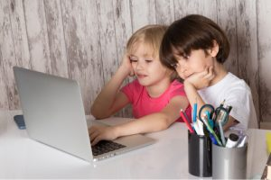 boy and girl stare at laptop appearing bored. how do you motivate children in distance learning is the question