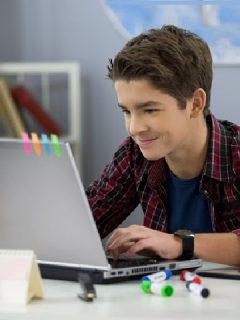 teenage boy using laptop with a smile motivated to study