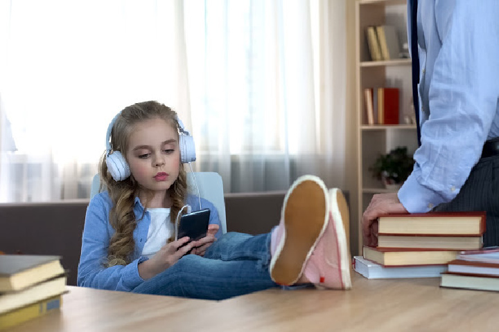 ten year old girl with headphones and feet on desk, dad stands over. removing natural consequence may make it a logical consequence instead.