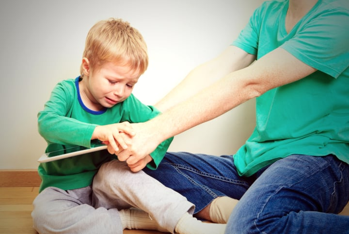 Boy cries and tries to get parents' fingers off iPad. Taking the iPad away is negative punishment.
