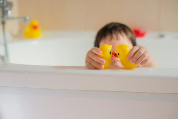 Child plays with two rubber ducks in bathtub - negative reinforcement