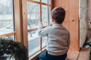 boy sitting in front of window in neglectful parenting