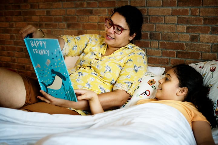 Woman wearing glasses reads bedtime story to child in bed, an example of operant conditioning.